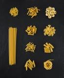 Auswahl von Teigwaren ungekocht, lokalisiert auf schwarzem Schieferhintergrund Lizenzfreies Stockfoto