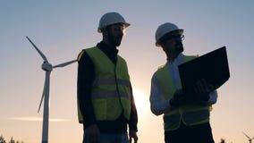 Auswechselbares electririty, grünes Energiekonzept Leute, die nahe Windmühlen zusammenarbeiten stock video footage