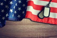 Ausweise der amerikanischen Flagge und der Soldaten auf hölzernem Hintergrund Lizenzfreies Stockbild