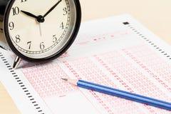 Auswertungsformular mit Bleistift und Wecker Stockfotos