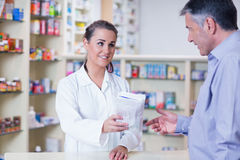 Auszubildender, der einem Kunden eine Tasche von Pillen gibt Stockfotos