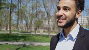 Auszubildender, der nach der Arbeit in Park, lächelnd mit Grübchen auf Gesicht geht stockfotografie