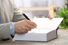 Autógrafo de assinatura do escritor no livro na tabela fotos de stock