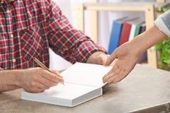 Autógrafo de assinatura do escritor no livro na tabela, fotografia de stock