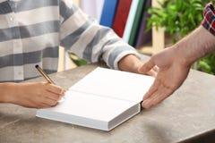 Autógrafo de assinatura do escritor no livro na tabela fotos de stock royalty free