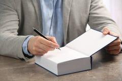 Autógrafo de assinatura do escritor no livro no tabl imagens de stock royalty free