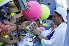 Autógrafos de firma de Kei Nishikori del jugador de tenis profesional después de la práctica para el US Open 2014 Foto de archivo