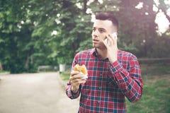 Autdoor antropófago joven hermoso del bocadillo Él está sosteniendo un teléfono Foto de archivo libre de regalías