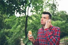Autdoor antropófago joven hermoso del bocadillo Él está sosteniendo un teléfono Imágenes de archivo libres de regalías