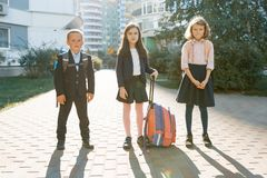 Outdoor portrait of smiling schoolchildren in elementary school. A group of kids with backpacks are having fun, talking. Education. Friendship, technology and stock images