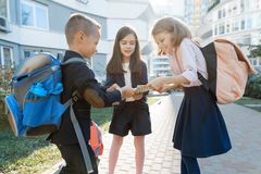 Outdoor portrait of smiling schoolchildren in elementary school. A group of kids with backpacks are having fun, talking. Education. Friendship, technology and royalty free stock photo