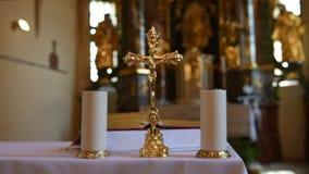 Autel dans l'église catholique avec la croix et bougies de tache floue au foyer banque de vidéos