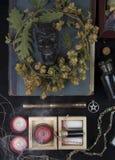 Autel occulte avec le visage du ` s de casserole, guirlande des houblon Photo stock
