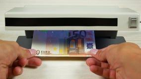 Autentificación del dinero en el detector Denominación del billete de banco de 50 euros debajo de la lámpara del detector metrajes