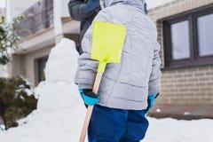 Autentisk familjvintergyckel Familj som bygger en snögubbe i deras frontyard Frank verklig folklivsstilbild royaltyfri foto
