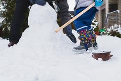 Autentisk familjvintergyckel Familj som bygger en snögubbe i deras frontyard Frank verklig folklivsstilbild arkivbilder