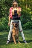 Autentisk kvinnalek med hunden för tysk herde i trädgård Arkivbild
