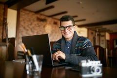 Autentisk stående av den unga le affärsmannen som i regeringsställning ser kameran med bärbara datorn Hipsterman i exponeringsgla Royaltyfria Bilder