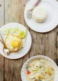 Autentisk thailändsk matställebakgrund: Kryddig soppa för Tom khagai, vanliga ris och blockkrapao med det stekte ägget överst på  fotografering för bildbyråer