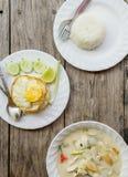 Autentisk thailändsk matställebakgrund: Kryddig soppa för Tom khagai, vanliga ris och blockkrapao med det stekte ägget överst på  royaltyfri foto