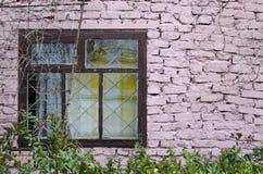 Autentyczna nadokienna rama wiejska chałupa z różową ścianą z cegieł i flowerpots wspinał się grungy ścianę zdjęcia royalty free