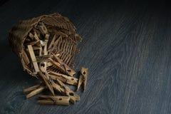 Autentyczni starzy drewniani clothespins w słomianym koszu na ciemnym drewnianym stole, zdjęcie royalty free
