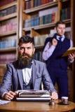 Auteur barbu avec le visage concentré dactylographiant sur une machine à écrire Photographie stock