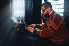 Auteur barbu en verres dactylographiant sur une machine à écrire Photographie stock libre de droits