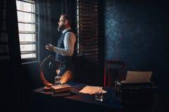 Auteur barbu en verres fumant une cigarette Image libre de droits