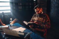 Auteur barbu en verres lisant un livre Photographie stock libre de droits