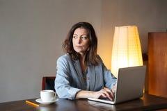 Auteur concentré de pensée de femme s'asseyant à l'intérieur utilisant l'ordinateur portable image stock