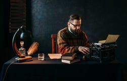 Auteur en verres dactylographiant sur la machine à écrire de vintage Photo stock