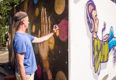 Auteur peignant un nouveau graffiti avec un pulvérisateur Photographie stock