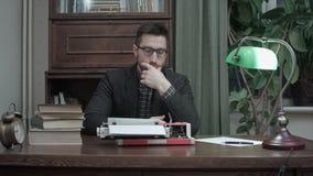 Auteur réfléchi s'asseyant devant l'inspiration de attente de machine à écrire pour son nouveau livre banque de vidéos