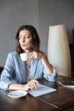 Auteur sérieux de pensée de femme s'asseyant à l'intérieur image libre de droits