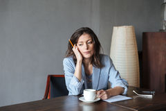 Auteur sérieux de pensée de femme s'asseyant à l'intérieur photo stock