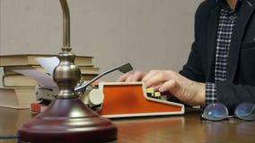 Auteur travaillant à la machine à écrire sur le bureau avec des livres et des verres banque de vidéos