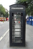 Authentic black English phone booth Royalty Free Stock Image