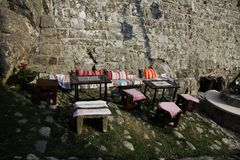 Authentic cafe along the road near stone wall. A few chairs and tables in a small authentic cafe Royalty Free Stock Image