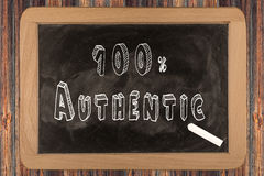 100% Authentic - chalkboard. With outlined text - on wood Stock Image
