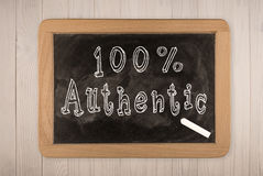 100% Authentic - chalkboard. With outlined text - on wood Royalty Free Stock Images