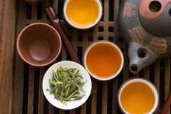 Authentic Chinese tea ceremony setting. Freshly brewed beverage poured in cups pot utensils on wooden tray. Loose tea leaves stock photo
