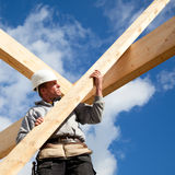 Authentic construction worker. Real carpenter at work with wooden  roof construction Royalty Free Stock Photo
