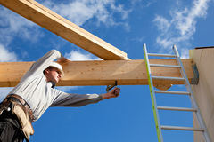 Authentic construction worker. Carpenter at work with wooden  roof construction Royalty Free Stock Photos