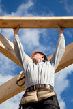 Authentic construction worker. Carpenter at work with wooden  roof construction Stock Images