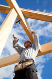 Authentic construction worker. Real builder at work with wooden construction Stock Photography