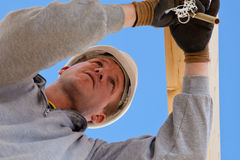 Authentic construction worker. Roofer at work with wooden  construction Royalty Free Stock Photo