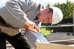 Authentic construction worker. Builder at work with wooden  construction and saw Stock Photo