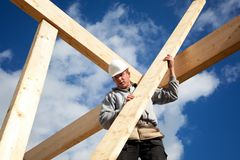 Authentic construction worker. Carpenter at work with wooden  roof construction Stock Photography