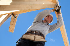 Authentic construction worker. Carpenter at work with wooden  roof construction Stock Photos